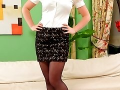 Gorgeous blonde in a tight white blouse and black miniskirt with sheer black pantyhose.
