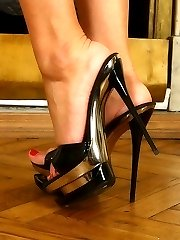 Busty blond beauty\'s stiletto heels almost pierce through slave\'s soft skin