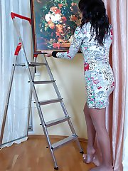 Sizzling hot chick hangs a picture before stripping her grey shiny pantyhose