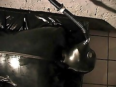 Mistress Brianna packs her sexy girl-slave in a tight latex cocoon suit with full air mask