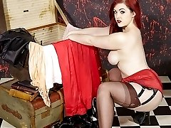 Strapon Jane bends this busty lesbian redhead over and fucks her pussy with a big red strapon