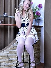 Curly blonde beauty smokes a cig before exposing white nylons and a girdle