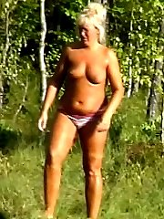 Tanned mature bitch walking topless near the lake. Enjoy the hot female!