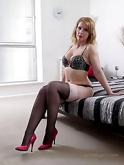 Horny Milf Jenny is waiting to seduce you on the bed in her sexy lingerie, stockings and high...
