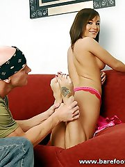 Barefoot hot chick strokes dick with her tattooed feet