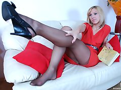 Seductive blondie lowers her smooth pantyhose while showing her yummy feet