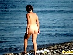 Nudist couple French-kissing on the beach