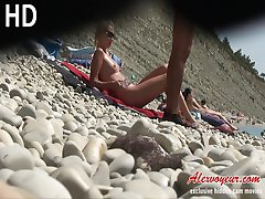The view of unshaved and shaved pussy of beautiful nudist babes relaxing on a beach is cool
