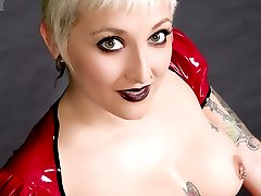 Tattooed and pierced blonde in red rubber glory