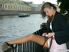 Leggy gal putting on her sheer glossy hose by the quay without being caught