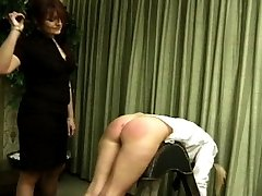She pulls one of the school girls across her knee and gives her a bare handed spanking, as her...