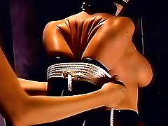 Heartless domina in latex gags a cute submissive woman then ropes her wrists