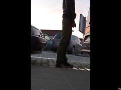 A quick piss stop behind a car