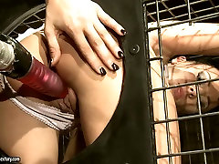 Torn slut is getting toy fucked hard sitting in a small cage. BDSM