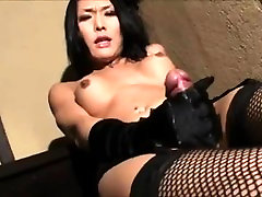 Asian shemale masturbates with her gloves on