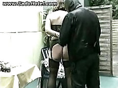 Mature slave getting tied to a gardenchair