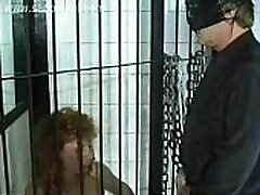 Slave with nice tits sitting in a jail is forced to suck cock of master and got peed on her body